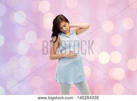 pregnancy, health, people and expectation concept - pregnant woman touching her neck and suffering from ache over rose quartz and serenity holidays lights background