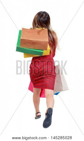 back view of a woman jumping with shopping bags. girl in red plaid dress runs away thrown on the back of paper shopping bags.