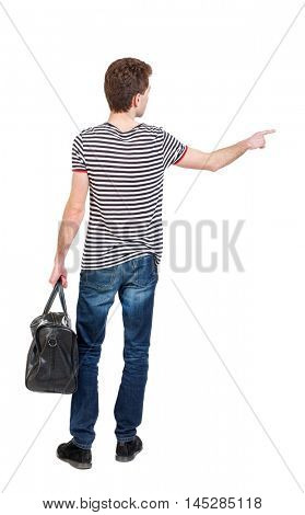 back view of pointing man with bag. Curly boy in a striped vest holding a bag in his hand and shows up finger.