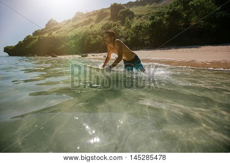 Shot of male surfer in the ocean water with surf board. Young man surfing in sea water.