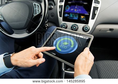 transport, business trip, technology and people concept - close up of male hands holding tablet pc computer with eco mode icon on screen in car