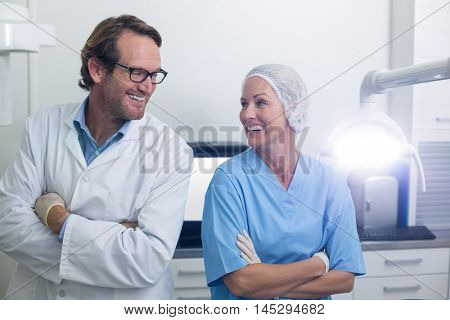Smiling dentist and dental assistant standing with arms crossed in dental clinic