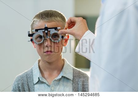 Optometrist examining young patient with phoropter in ophthalmology clinic
