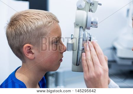 Young patient under going eye test through phoropter in ophthalmology clinic