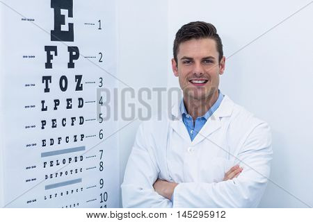 Portrait of handsome optometrist standing with arms crossed in ophthalmology clinic