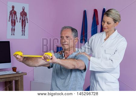 Senior man training with exercise band assisted by physiotherapist in clinic