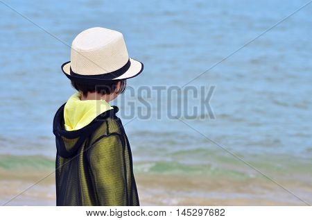 Small kid with hat and jacket on the sea. Four years old.