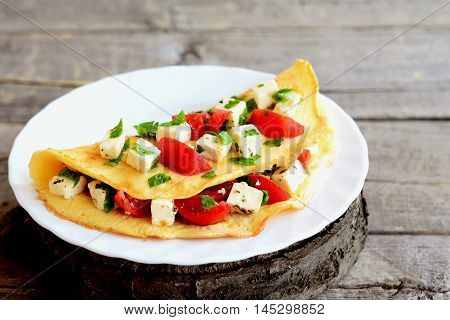 Fried omelet stuffed with cheese, tomatoes and parsley. Stuffed omelette on a plate and on old wooden background. Easy egg omelet recipe. Closeup