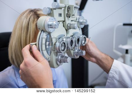 Female patient under going eye test through phoropter in ophthalmology clinic