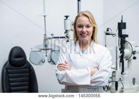 Portrait of female optometrist standing with arms crossed in ophthalmology clinic