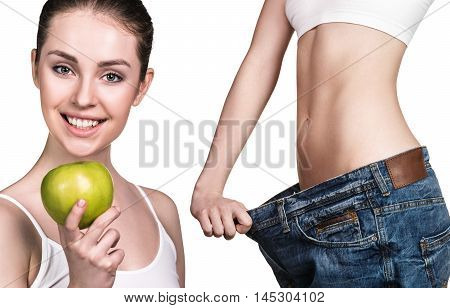 Young slim woman holding an apple and wearing oversize jeans over white background