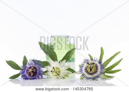 Passion flower with aromatherapy essential oil blue glass bottler isolated over white background.