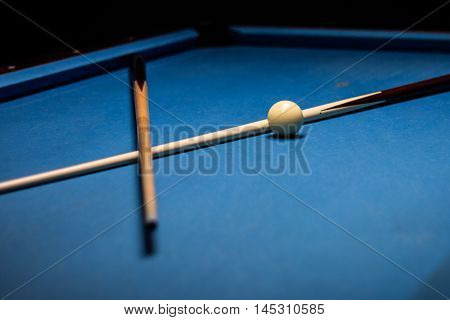 Two pool sticks and a white cue ball on a billiards table covered in blue felt.