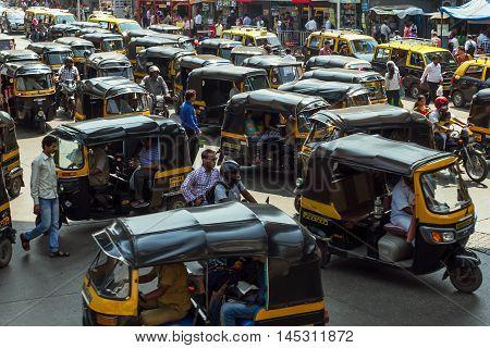 MUMBAI, INDIA - MARCH 14, 2015: Tuk tuks and other vehicles navigate the traffic.