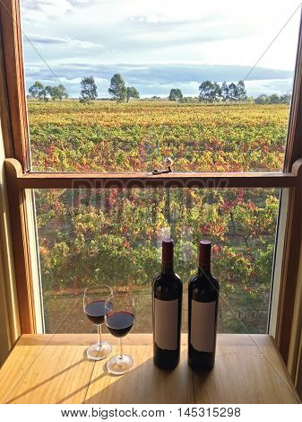 Glass of red wine next to bottles near windows with soft view of vineyard in afternoon. These wine grapes are growing on limestone coast in Coonawarra winery region during Autumn in South Australia
