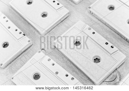 Audio cassettes are covered with white acrylic paint. Pictures taken at an angle. Black and white photo. Excellent retro. Creative decor. Sepia effect. Secured by modern style. Vintage tapes.