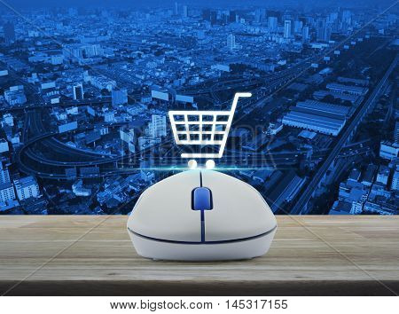 Wireless computer mouse with on line shopping icon on wooden table over city tower street and expressway