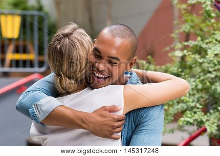 Happy smiling african man hugging young woman outside cafe. Attractive young couple hugging each other and smiling. Happy friends laughing and hugging outdoor.