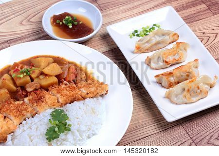 Rice with deep fried dolly fish in japanese yellow curry and side dish of stuffing flour.