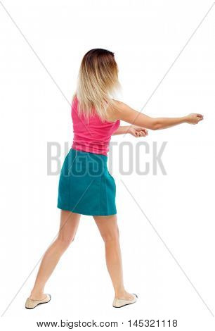 back view of standing girl pulling a rope from the top or cling to something. Isolated over white background. Blonde in a red sweater and green skirt pulling rope.