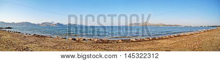 Bay of Pollenca panorama - beach with seaweed in front - peninsula Formentor on the left peninsula Victoria on the right north of Majorca