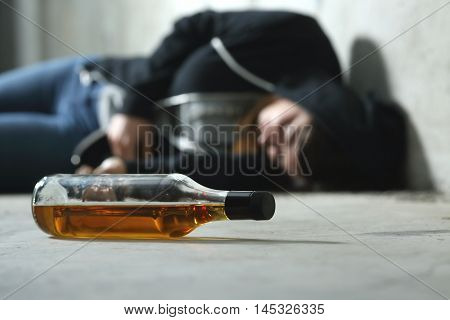 Drunk teenager on the floor in a dark and sad place and an alcohol bottle in the foreground