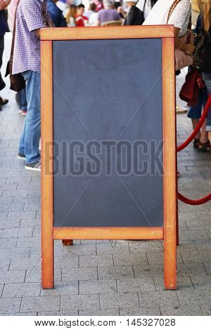 blank blackboard pavement sign with unrecognizable people in the background. also known as customer stopper or sandwich board.