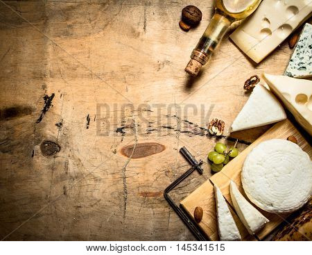 White wine with different types of cheese. On a wooden table.