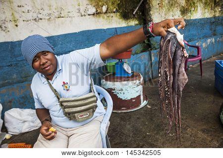 SANTO DOMINGO ECUADOR - APRIL 15 2010: Unidentified man selling octopus seafood market in Santo Domingo Ecuador.