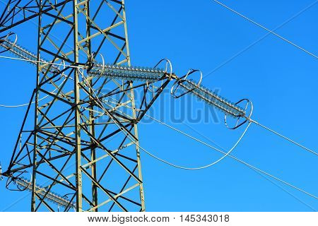 Detail of a high voltage tower (power line) with electric cables and insulators on a clear blue sky