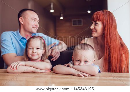 Happy family waiting for the order in a restaurant