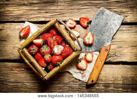 Strawberries in a basket with a hatchet. On a wooden table.