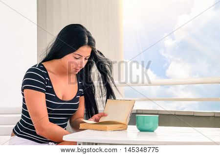 Young woman reading book with tea cup on table - Beautiful girl studying at home sitting on terrace with white clouds sky as background - Concept of female relax in peaceful and candid ambience