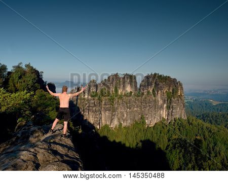 Climber In Black Pants Gesture Of Triumph. Body Naked Man On Rock