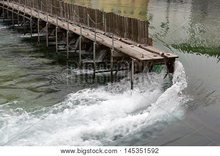 Lucerne Switzerland - May 11 2016: Needle Dam in the river Reuss. Weir was designed to use of thin wooden needles that can be added or removed by hand to maintain the level of water in Lake Lucerne. The Needle Dam is located in the old town of Lucerne. Lu