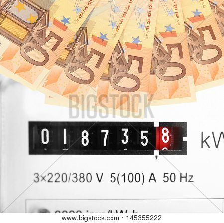 Euro banknotes and electric meter display background.