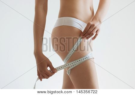 fit young woman measuring her waistline grey blurred background with a space for your text.