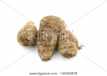 Pile of small brown taro with root hair on isolated white background