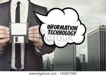 Information technology text on speech bubble with businessman holding diskette