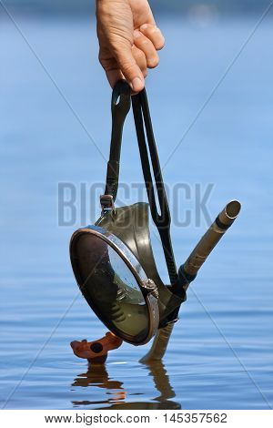 hands holding old diving mask on water background
