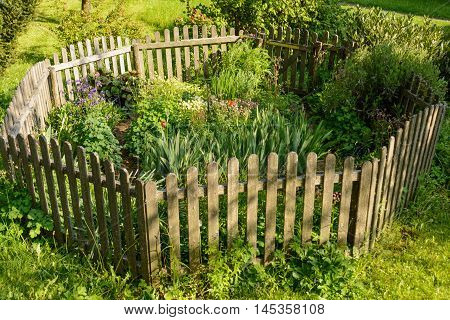 idyllic small flower garden fenced octagonal wooden fence