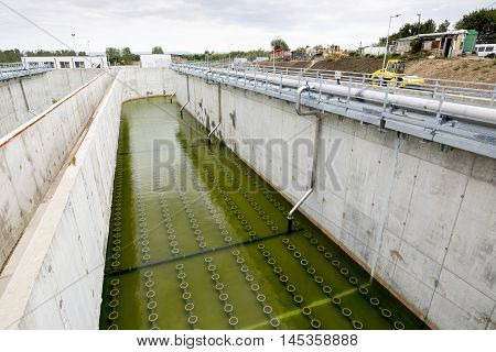 Sludge Recirculation Clarifier Solid Contact Sedimentation Tank. Green dirty water. Wastewater treatment plant. Wastewater treatment is a process used to convert dirty wastewater into an effluent that can be either returned to the water cycle with minimal poster