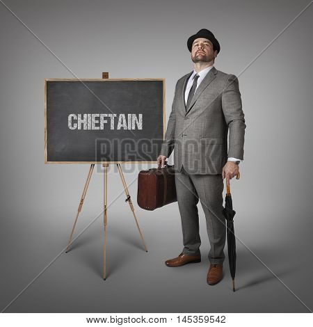 Chieftain text on  blackboard with businessman holding umbrella and suitcase