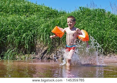 Happy boy bathes in the river on a summer day