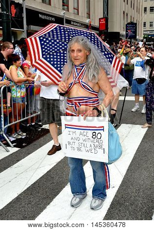 New York City - June 25 2011: 80 year old would-be bride with patriotic umbrella at the 2011 Gay Pride Parade on Fifth Avenue