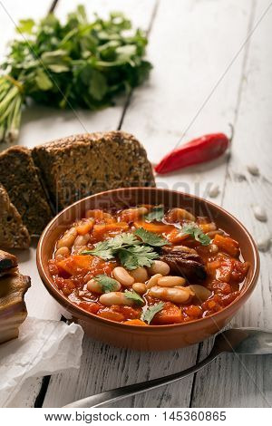 Rustic Kidney Bean Soup with beans and carrot. On the white wooden table