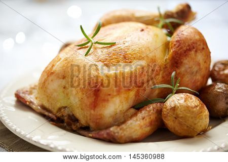 Whole Roasted Chicken on dinner table. Holidays.