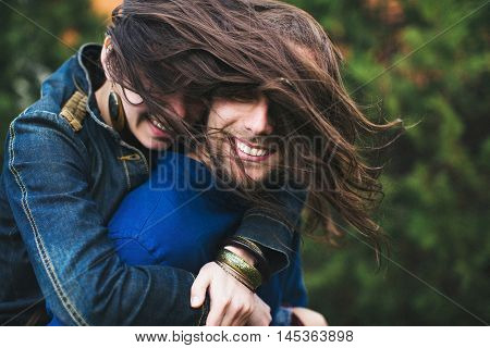Girl hugs her boyfriend her hair windblown. Portrait of a beautiful young couple.