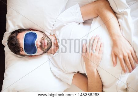 Man Lying On A Bed With Sleep Mask