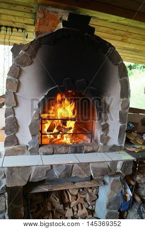 Oven barbecue decorated with a decorative stone with a fire in the hearth and wood on the stand